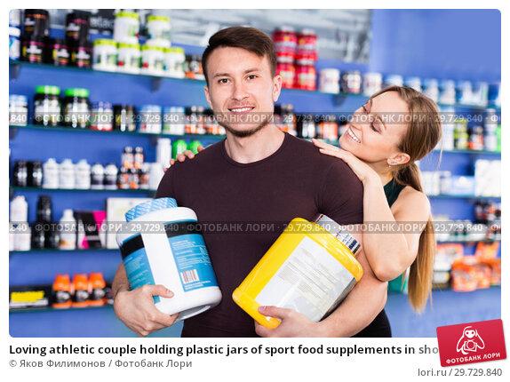 Купить «Loving athletic couple holding plastic jars of sport food supplements in shop interior», фото № 29729840, снято 12 апреля 2018 г. (c) Яков Филимонов / Фотобанк Лори