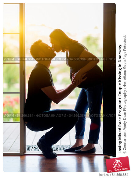 Loving Mixed Race Pregnant Couple Kissing in Doorway. Стоковое фото, фотограф Zoonar.com/Andy Dean Photography / age Fotostock / Фотобанк Лори