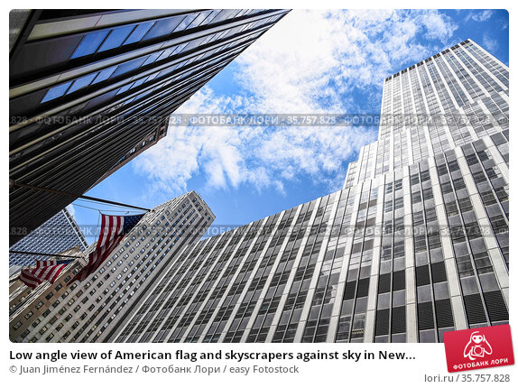 Low angle view of American flag and skyscrapers against sky in New... Стоковое фото, фотограф Juan Jiménez Fernández / easy Fotostock / Фотобанк Лори