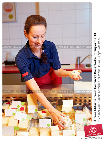 Ältere Mitarbeiterin bestückt Käsetheke im Supermarkt. Стоковое фото, фотограф Zoonar.com/Robert Kneschke / age Fotostock / Фотобанк Лори