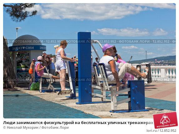Купить «Люди занимаются физкультурой на бесплатных уличных тренажерах на набережной курорта Геленджика», фото № 12852952, снято 19 июля 2015 г. (c) Николай Мухорин / Фотобанк Лори