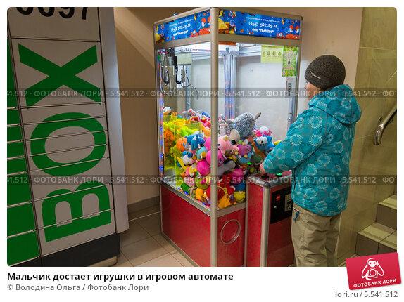 Купить «Мальчик достает игрушки в игровом автомате», эксклюзивное фото № 5541512, снято 26 декабря 2013 г. (c) Володина Ольга / Фотобанк Лори