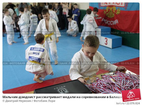 Купить «Мальчик-дзюдоист рассматривает медали на соревновании в Балашихе», эксклюзивное фото № 22076824, снято 6 марта 2016 г. (c) Дмитрий Неумоин / Фотобанк Лори