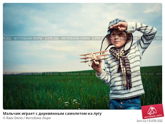 Купить «Мальчик играет с деревянным самолетом на лугу», фото № 5070332, снято 13 июля 2013 г. (c) Raev Denis / Фотобанк Лори