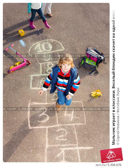 Мальчик играет в классики. Веселый блондин скачет на одной ноге. Стоковое фото, фотограф Сергей Новиков / Фотобанк Лори