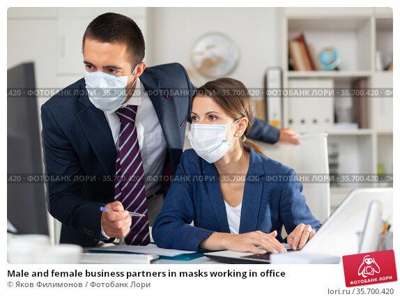Male and female business partners in masks working in office. Стоковое фото, фотограф Яков Филимонов / Фотобанк Лори