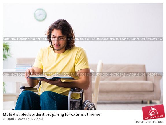 Male disabled student preparing for exams at home. Стоковое фото, фотограф Elnur / Фотобанк Лори