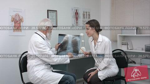 Купить «Male doctor explaining lungs x-ray to female doctor in the medical office.», видеоролик № 28577604, снято 20 июня 2016 г. (c) Vasily Alexandrovich Gronskiy / Фотобанк Лори