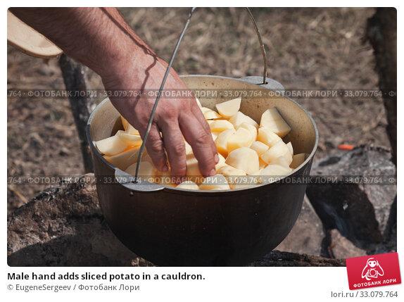 Купить «Male hand adds sliced potato in a cauldron.», фото № 33079764, снято 14 июля 2019 г. (c) EugeneSergeev / Фотобанк Лори
