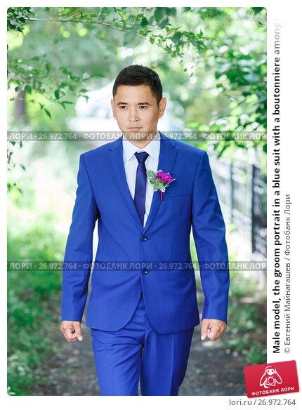 Купить «Male model, the groom portrait in a blue suit with a boutonniere among the green foliage on a wedding day», фото № 26972764, снято 31 июля 2015 г. (c) Евгений Майнагашев / Фотобанк Лори