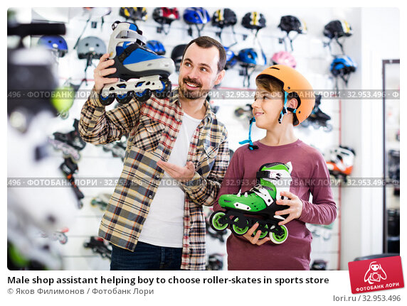 Male shop assistant helping boy to choose roller-skates in sports store. Стоковое фото, фотограф Яков Филимонов / Фотобанк Лори