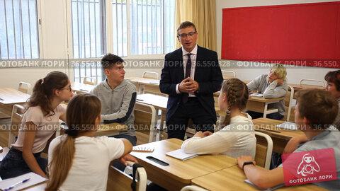 Male teacher standing at whiteboard in classroom, conducting lesson with teen students. Стоковое видео, видеограф Яков Филимонов / Фотобанк Лори