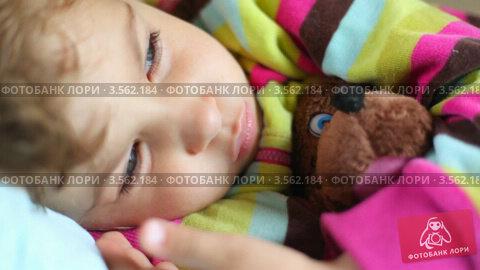 Купить «Маленькая девочка лежит в постели, обняв игрушечного медведя», видеоролик № 3562184, снято 3 января 2010 г. (c) Losevsky Pavel / Фотобанк Лори