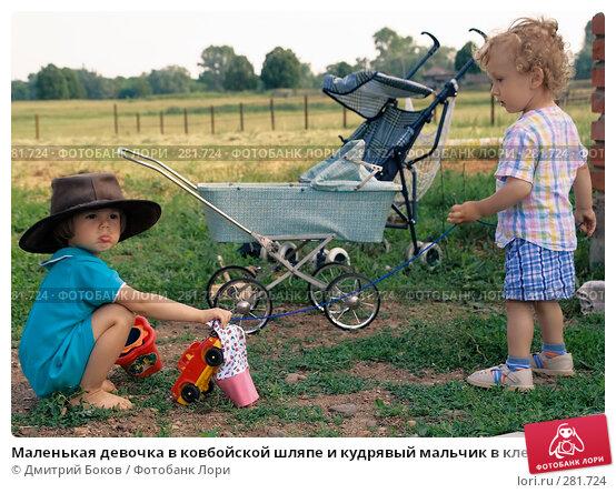 Маленькая девочка в ковбойской шляпе и кудрявый мальчик в клетчатых шортах играют на зеленой лугу в деревне, фото № 281724, снято 25 июня 2006 г. (c) Дмитрий Боков / Фотобанк Лори