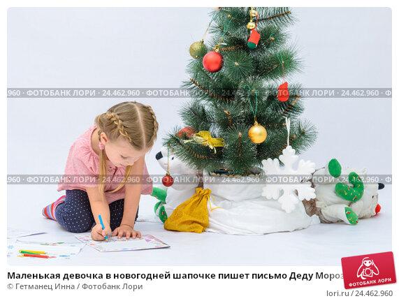 Купить «Маленькая девочка в новогодней шапочке пишет письмо Деду Морозу рядом с елкой», фото № 24462960, снято 9 декабря 2016 г. (c) Гетманец Инна / Фотобанк Лори