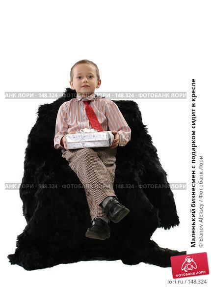 Купить «Маленький бизнесмен с подарком сидит в кресле», фото № 148324, снято 1 декабря 2007 г. (c) Efanov Aleksey / Фотобанк Лори
