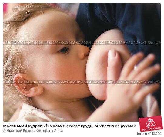 Маленький кудрявый мальчик сосет грудь, обхватив ее руками, фото № 248220, снято 8 мая 2006 г. (c) Дмитрий Боков / Фотобанк Лори
