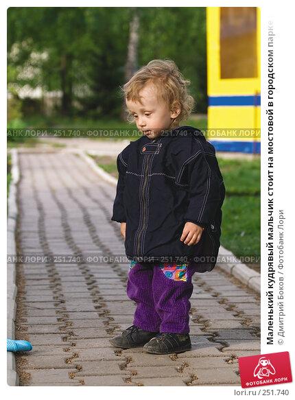 Маленький кудрявый мальчик стоит на мостовой в городском парке и смотрит на брошенную им голубую шапку, фото № 251740, снято 20 мая 2006 г. (c) Дмитрий Боков / Фотобанк Лори