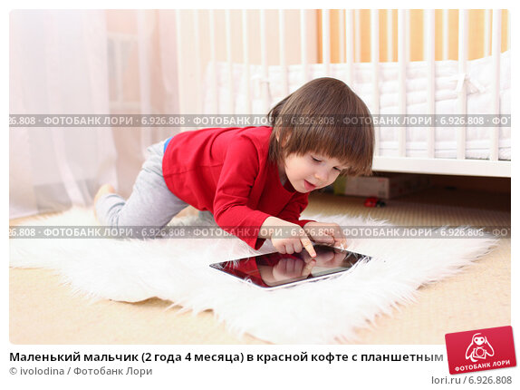 Маленький мальчик (2 года 4 месяца) в красной кофте с планшетным компьютером, фото № 6926808, снято 21 января 2015 г. (c) ivolodina / Фотобанк Лори