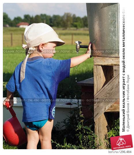 Маленький мальчик играет с водой около металлического бака с краном, фото № 296484, снято 16 июля 2006 г. (c) Дмитрий Боков / Фотобанк Лори