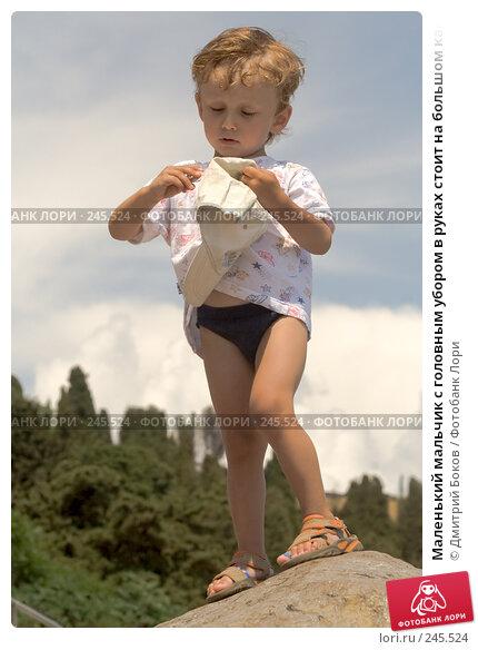 Маленький мальчик с головным убором в руках стоит на большом камне на фоне предгрозового неба, фото № 245524, снято 20 июня 2007 г. (c) Дмитрий Боков / Фотобанк Лори