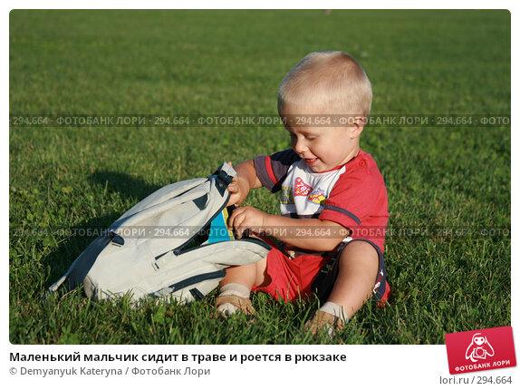 Маленький мальчик сидит в траве и роется в рюкзаке, фото № 294664, снято 27 июня 2007 г. (c) Demyanyuk Kateryna / Фотобанк Лори