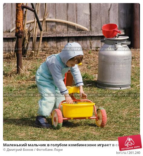 Маленький мальчик в голубом комбинезоне играет в сельском дворе с трехколесным велосипедом (1), фото № 261240, снято 20 апреля 2008 г. (c) Дмитрий Боков / Фотобанк Лори