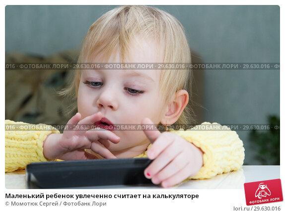 Купить «Маленький ребенок увлеченно считает на калькуляторе», фото № 29630016, снято 30 декабря 2018 г. (c) Момотюк Сергей / Фотобанк Лори