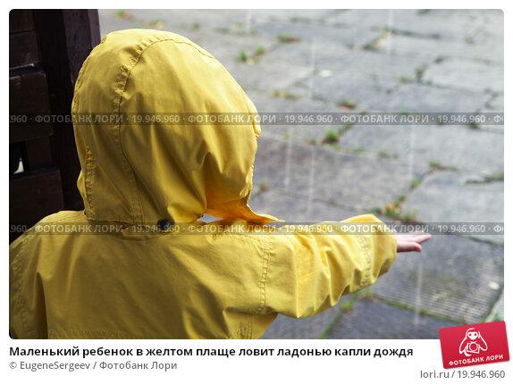 Купить «Маленький ребенок в желтом плаще ловит ладонью капли дождя», фото № 19946960, снято 21 сентября 2015 г. (c) EugeneSergeev / Фотобанк Лори