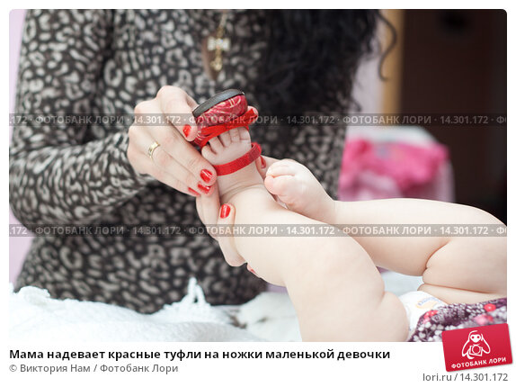 Мама надевает красные туфли на ножки маленькой девочки. Стоковое фото, фотограф Виктория Нам / Фотобанк Лори