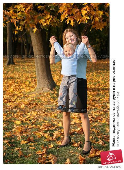 Купить «Мама подняла сына за руки в парке осенью», фото № 261092, снято 26 апреля 2018 г. (c) Losevsky Pavel / Фотобанк Лори