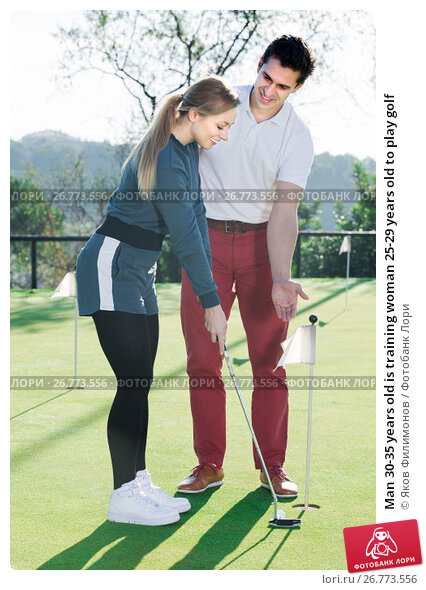 Купить «Man 30-35 years old is training woman 25-29 years old to play golf», фото № 26773556, снято 27 мая 2018 г. (c) Яков Филимонов / Фотобанк Лори