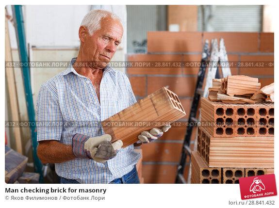 Купить «Man checking brick for masonry», фото № 28841432, снято 19 июня 2018 г. (c) Яков Филимонов / Фотобанк Лори