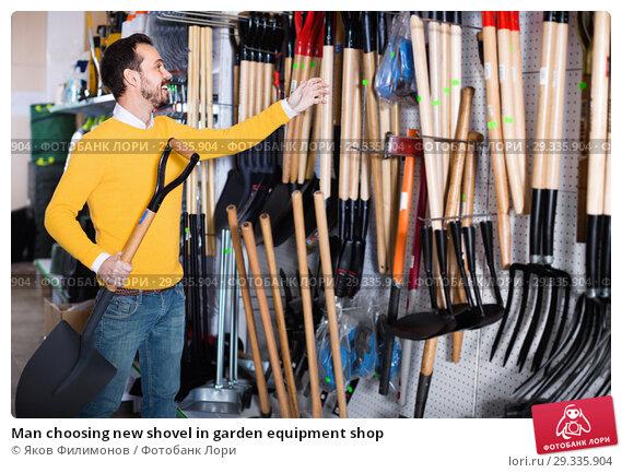Купить «Man choosing new shovel in garden equipment shop», фото № 29335904, снято 2 марта 2017 г. (c) Яков Филимонов / Фотобанк Лори