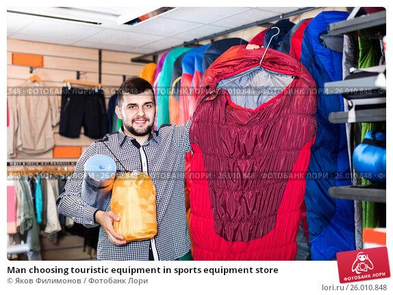 Man choosing touristic equipment in sports equipment store ...