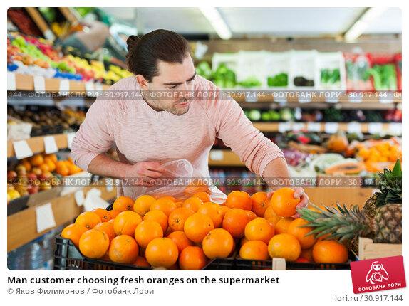 Купить «Man customer choosing fresh oranges on the supermarket», фото № 30917144, снято 27 апреля 2019 г. (c) Яков Филимонов / Фотобанк Лори