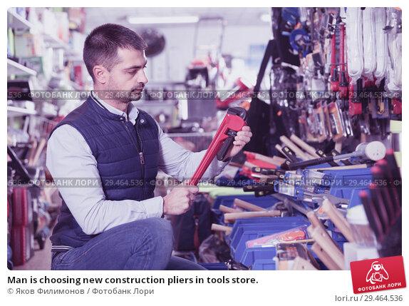 Купить «Man is choosing new construction pliers in tools store.», фото № 29464536, снято 9 января 2018 г. (c) Яков Филимонов / Фотобанк Лори