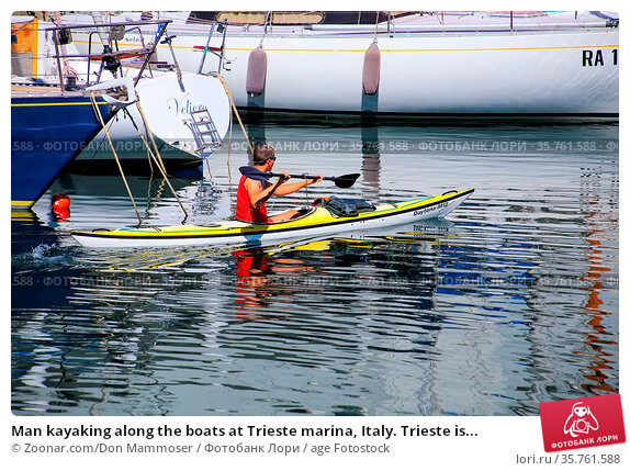 Man kayaking along the boats at Trieste marina, Italy. Trieste is... Стоковое фото, фотограф Zoonar.com/Don Mammoser / age Fotostock / Фотобанк Лори
