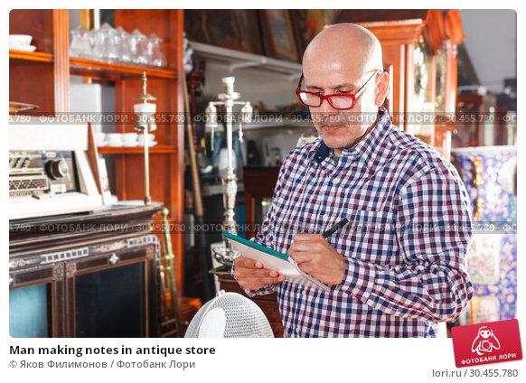 Man making notes in antique store. Стоковое фото, фотограф Яков Филимонов / Фотобанк Лори