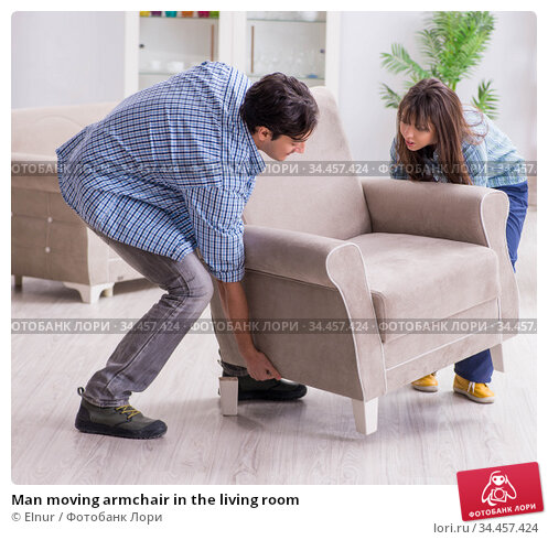 Man moving armchair in the living room. Стоковое фото, фотограф Elnur / Фотобанк Лори