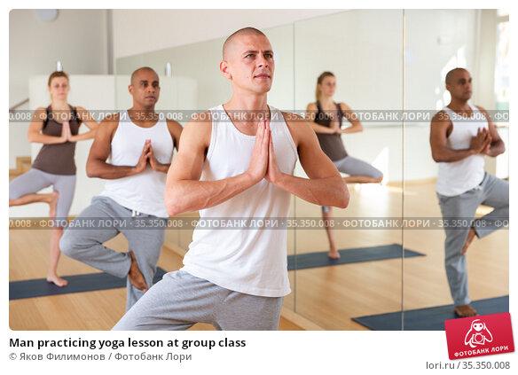 Man practicing yoga lesson at group class. Стоковое фото, фотограф Яков Филимонов / Фотобанк Лори