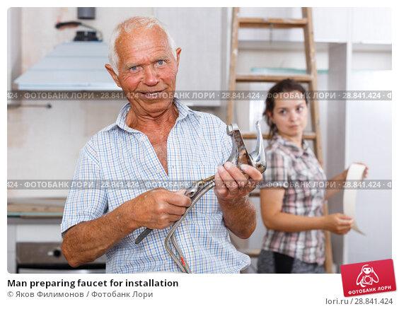 Купить «Man preparing faucet for installation», фото № 28841424, снято 19 июня 2018 г. (c) Яков Филимонов / Фотобанк Лори
