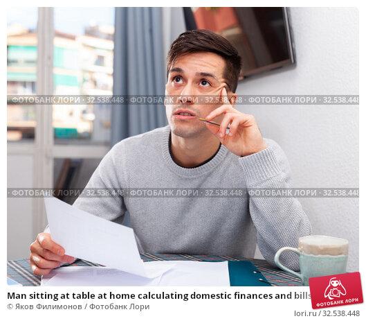 Купить «Man sitting at table at home calculating domestic finances and bills», фото № 32538448, снято 10 декабря 2019 г. (c) Яков Филимонов / Фотобанк Лори