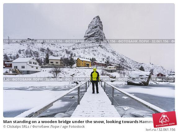 Man standing on a wooden bridge under the snow, looking towards Hammarskaftet peak. Reine, Nordland county, Northern Norway, Norway. Стоковое фото, фотограф Clickalps SRLs / age Fotostock / Фотобанк Лори