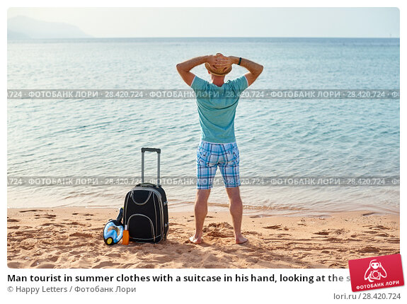 Купить «Man tourist in summer clothes with a suitcase in his hand, looking at the sea on the beach, concept of time to travel», фото № 28420724, снято 19 апреля 2018 г. (c) Happy Letters / Фотобанк Лори