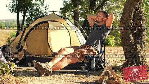 Купить «Man tourist resting on chair in front of tent», видеоролик № 29030072, снято 30 августа 2018 г. (c) Илья Шаматура / Фотобанк Лори