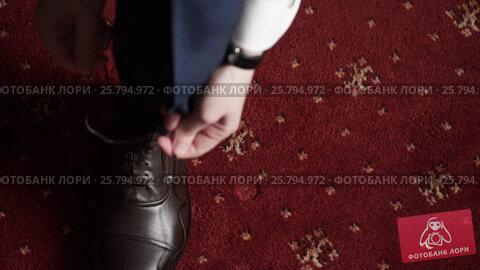Man wearing shoes, tie the laces, видеоролик № 25794972, снято 2 марта 2016 г. (c) Алексей Макаров / Фотобанк Лори