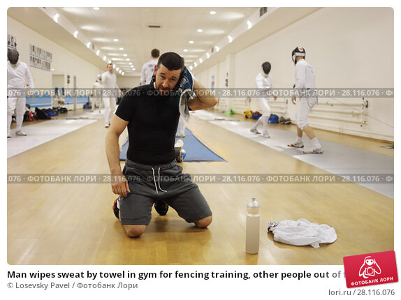 Купить «Man wipes sweat by towel in gym for fencing training, other people out of focus», фото № 28116076, снято 9 февраля 2017 г. (c) Losevsky Pavel / Фотобанк Лори