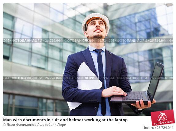 Купить «Man with documents in suit and helmet working at the laptop», фото № 26724044, снято 29 апреля 2017 г. (c) Яков Филимонов / Фотобанк Лори