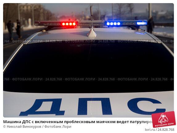 Купить «Машина ДПС с включенным проблесковым маячком ведет патрулирование на улице города», фото № 24828768, снято 8 января 2017 г. (c) Николай Винокуров / Фотобанк Лори